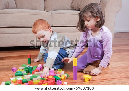 Two kids playing with blocks in front of couch - stock photo