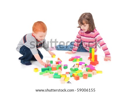 Two kids playing with colorful blocks. Isolated on white with shadows. - stock photo