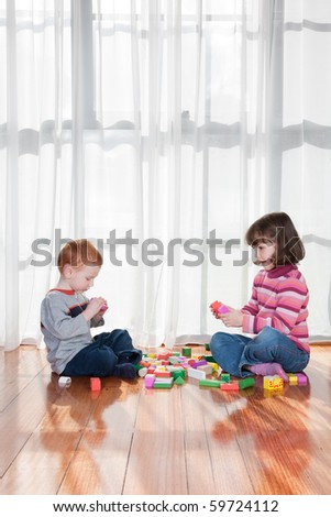Two kids playing with wooden blocks in front of window - stock photo