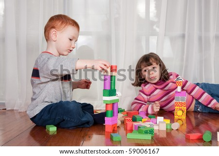 Two kids playing with wooden blocks on polished floor with window behind - stock photo