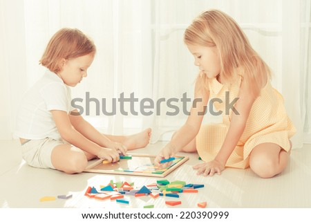 two kids playing with wooden mosaic in their room on the floor - stock photo