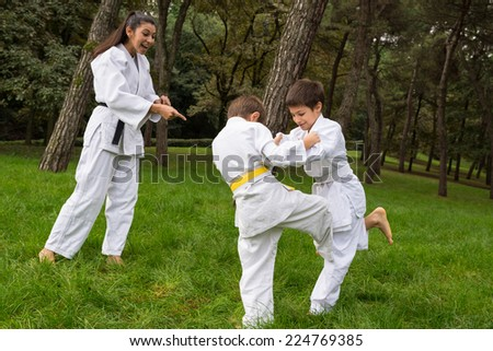 Two kids practicing judo outdoors in a park under the supervision of a master. - stock photo