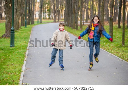 Two kids riding in autumn park on roller skates together
