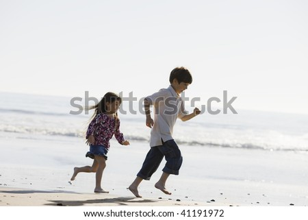 Two Kids Running Barefoot on the Sand at The Beach - stock photo