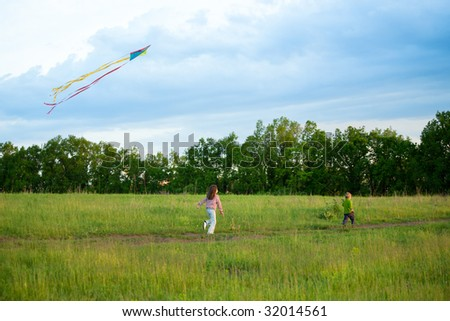 Two kids running on a meadow and fly a kite - stock photo