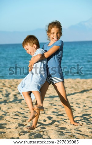 Two kids - seven and three on the beach playing. Sister is lifting and spinning around her younger brother laughing. - stock photo