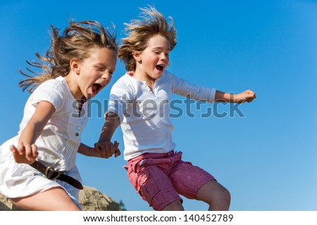 Two kids shouting and jumping together outdoors. - stock photo