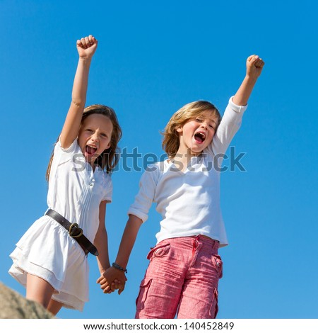 Two kids shouting and raising hands outdoors, - stock photo