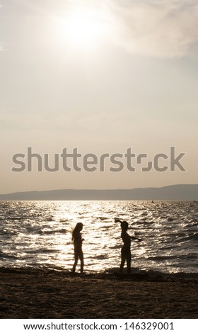 two kids silhouettes playing on beach at sunset