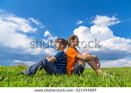 Two kids sitting back-to-back on green grass against blue sky