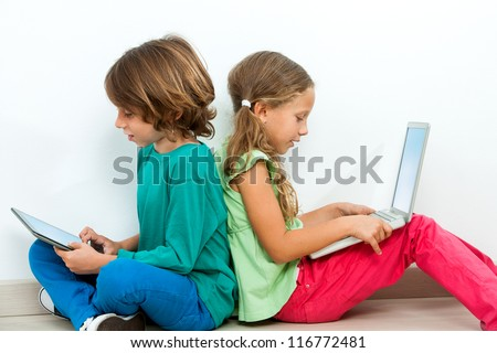 Two kids sitting back to back socializing with laptop and tablet. - stock photo