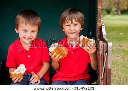 Two kids, sitting in a sheltered bench, eating sandwiches, outdoor summertime - stock photo