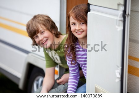 Two Kids Sitting In Doorway Of RV - stock photo