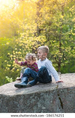 Two kids sitting together on a rock in the light of a warm , sunny day in spring and having fun.