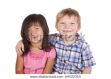 Two kids sitting together with different ethnic backgrounds. - stock photo