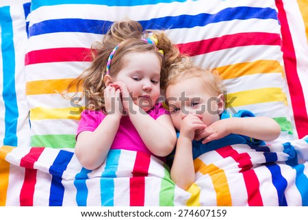 Two kids sleeping in bed under colorful blanket. Children relaxing in bedroom. Tired toddler girl and baby boy before bedtime. Rainbow textile bedding for nursery. Brother and sister play at home. - stock photo