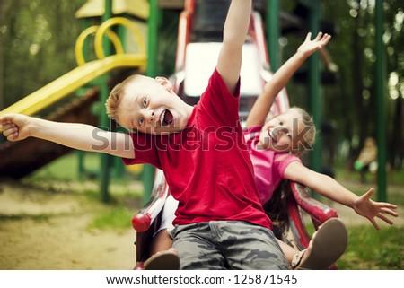 Two kids slide on playground - stock photo