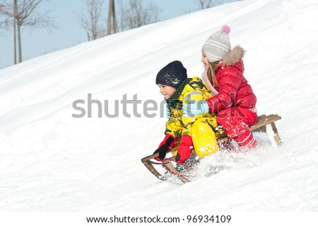 Two kids sliding with sledding in the snow. - stock photo