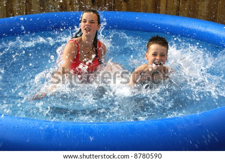 Two kids splashing in pool.