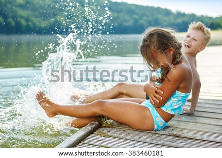 Two kids splashing water with their feet in summer - stock photo