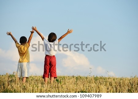 Two kids standing on meadow with arms up in air - stock photo