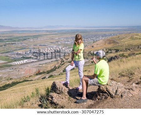 Two kids talking on a background of the industrial landscape. Salt Lake City, Utah - stock photo