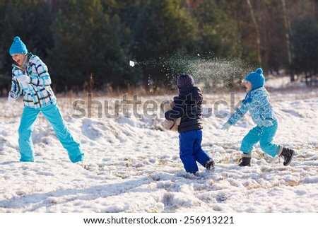Two kids throwing snowballs at their mother outdoors on a snowy winter's day - stock photo