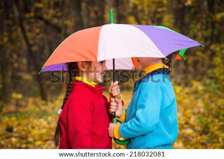 Two kids together under umbrella in autumn park - stock photo