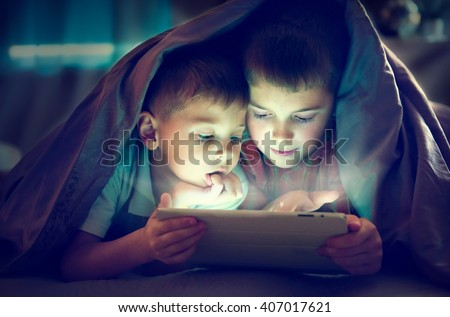 Two kids using tablet pc under blanket at night. Brothers with tablet computer in a dark room - stock photo