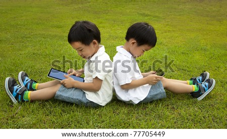 Two kids using touchscreen tablet PC on the grass - stock photo