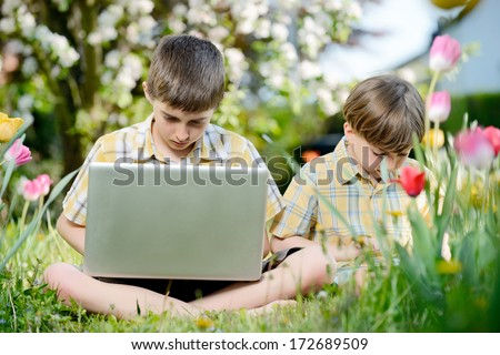 Two kids using touchscreen tablet PC outdoors in spring park - stock photo
