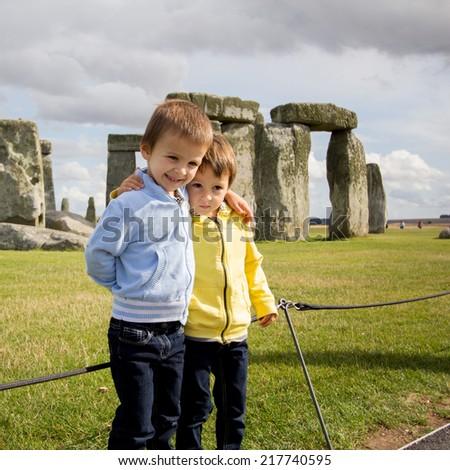 Two kids, visiting Stonehenge at daytime - stock photo