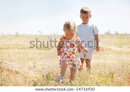 two kids walking on rural background - stock photo