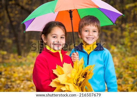 Two kids walking together on autumn park - stock photo