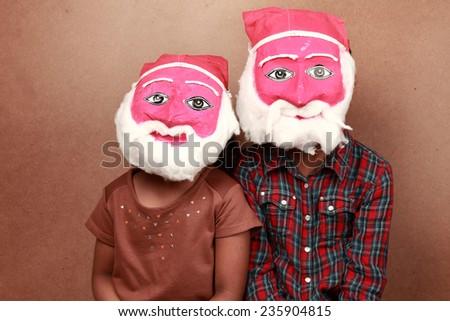 Two kids wear hand made masks of Santa - stock photo