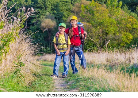 Two kids with backpacks traveling together through a meadow