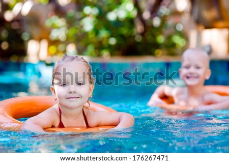 Two kids with lifebuoy in swimming pool - stock photo