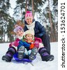 Two kids with mother is sledging in winter-landscape - stock photo