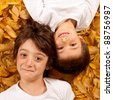 Two kids - 6 year old - laughing, lying on autumn leaves. - stock photo