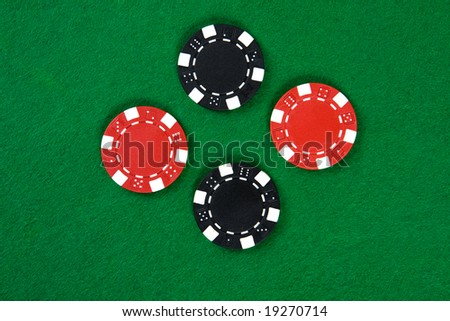 Two kinds of poker chips in the middle of green poker table. Top view.