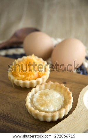 two kinds of sweet mini tarts on wooden board - stock photo