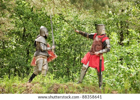 Two knights in armor fights in forest - stock photo