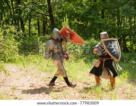 Two knights in armor is fighting  at forest