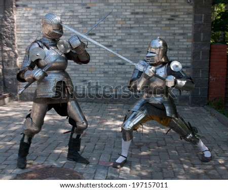 two knights in the ancient metal armor - stock photo