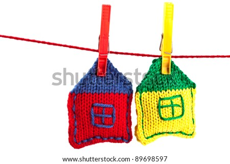 two knitted colorful houses on a red string isolated on white background - stock photo