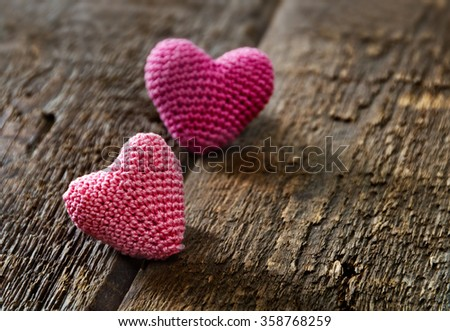 Two knitting hearts on old wooden panel. Background Valentines Day.Valentines day cards. - stock photo