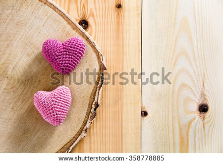 Two knitting hearts on old wooden panel. Background Valentines Day.Valentines day cards.