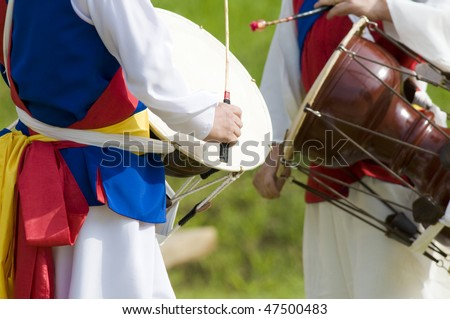 Two Korean drummers playing the traditional hourglass-shaped drum (janggu). - stock photo