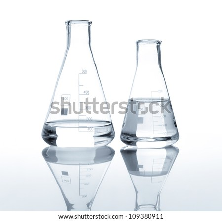 Two laboratory flasks with a clear liquid, isolated - stock photo