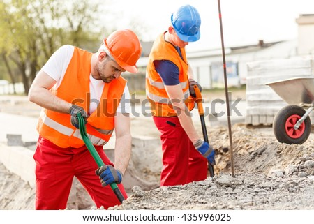 Two labourers working very hard with shovels - stock photo
